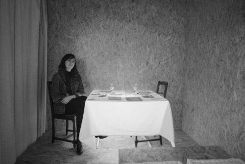 Paula Petit dans son installation, La femme gelée, 2019, installation, acrylique rétroéclairée, tirages sur papiers mixtes, coton brodé, argenterie, 1 m x 1 m.